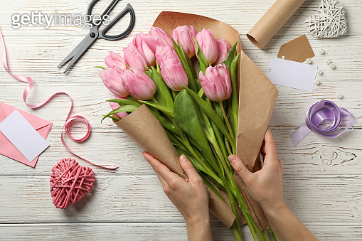 Girl packs tulips in craft paper on wooden background, top view