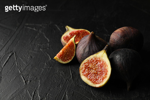 Fresh fig fruits and slices on black background