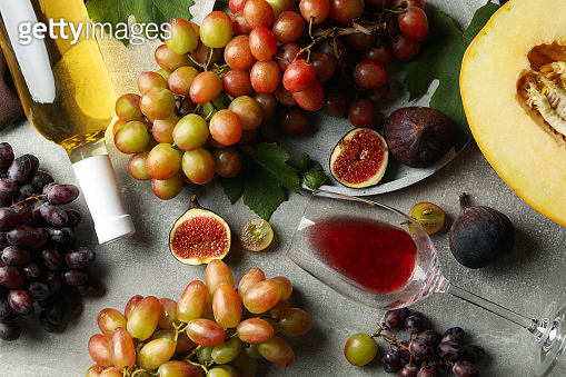Composition with grape, wine, fig and melon on gray background