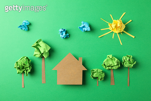 Paper house, clouds, sun and trees on green background, top view