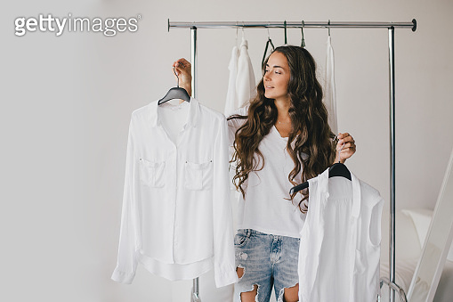 Beautiful young woman stylist standing near rack with hangers with white clothes. Shopaholic with many clothes.