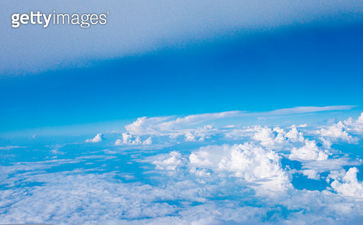 Blue sky with clouds and sun on airplane view.