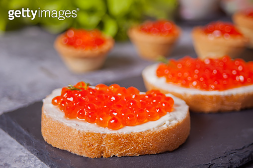 Fresh red caviar on bread on the black plate. Sandwiches with red caviar. Delicatessen. Gourmet food.