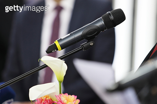 Microphone in focus against blurred unrecognizable business person at business conference