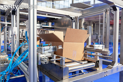 Cardboard package box at automated packaging line in the warehouse or distribution centre