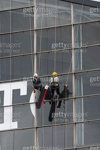 Two men are working on glass from outside the skyscraper in la Defense, Paris, France.Nike Logo On The Windows