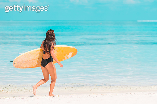 Beautiful surfer woman ready to surfing in turquoise sea, on stand up paddle board at exotic vacation