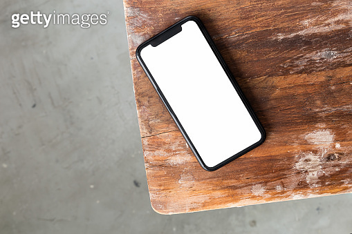 Top view mockup telephone device screen on a wooden table
