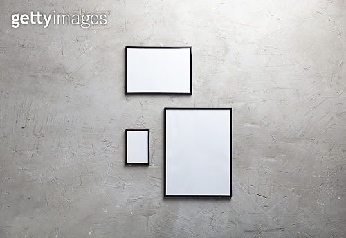 Three empty photo frame hanging on a cement wall. Mock up for adding your text