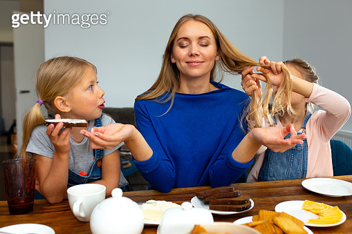 Smiling mother having breakfast with cheerful daughters