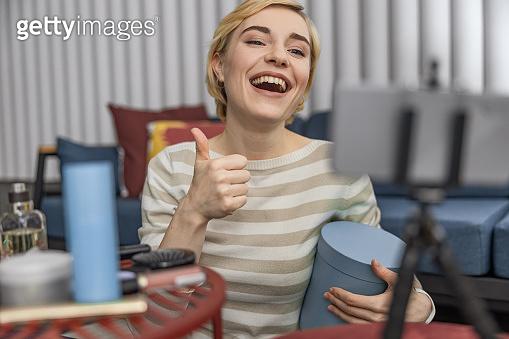 Happy female blogger showing box on camera