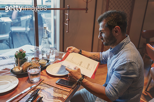 Man checking out of restaurant menu, ordering food