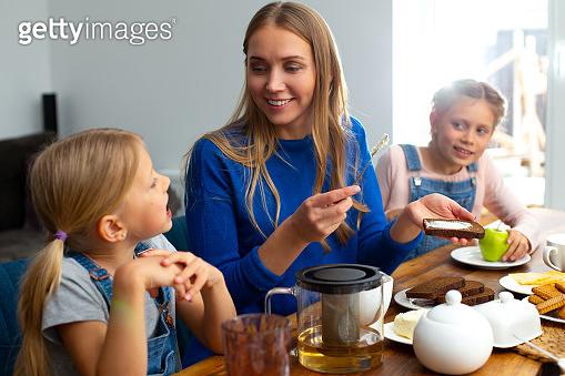 Happy mother enjoying breakfast with adorable kids