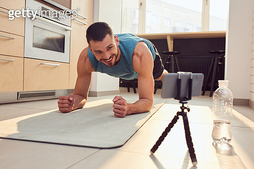 Joyful sportsman working out and using cellphone at home