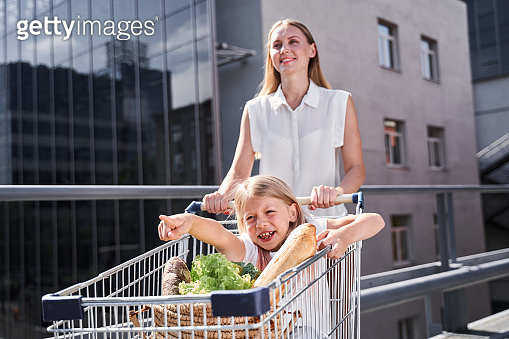 Cheerful mother and daughter after buying food stuff
