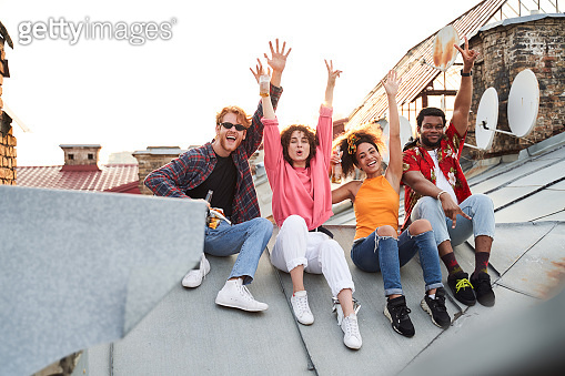 Jolly four friends having fun on roof