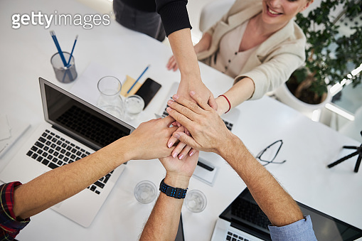 Business colleagues putting their hands together in office