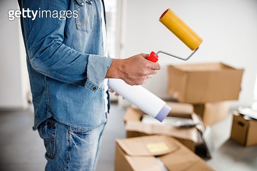 Man in denim decorating flat with wall paper