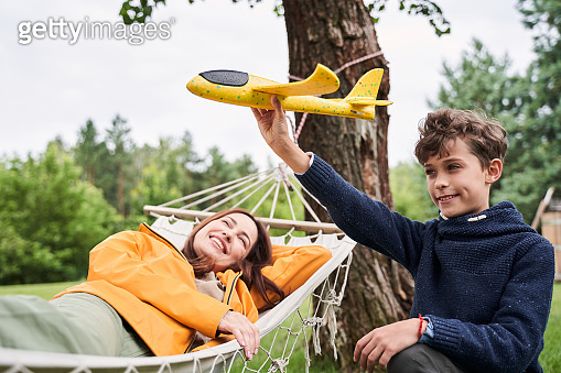 Loving mother spending time with adorable son outdoors