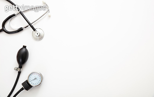 Medical stethoscope and sphygmomanometer on white background, top view.