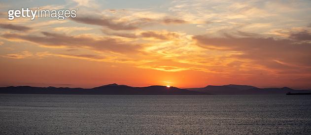 Sunrise, sunset clouds. Twilight, dusk cloudy sky over sea water, dark land horizon