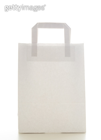 Carrying goods concept. One, white, blank, ecological, reusable paper shopping bag with handles isolated cutout on white background. Copyspace, vertical photo.