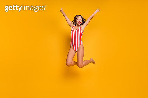 Full length photo of beautiful lady slim bronze body beach pool jumping high up into water crazy good mood rejoicing wear white red striped bodysuit isolated yellow color background