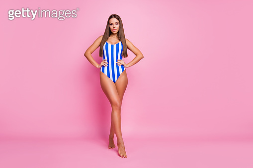 Full length photo of gentle hot figure body lady fit legs perfect hairstyle long straight hair arms by sides wear white blue striped bodysuit isolated pastel pink color background