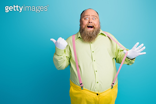 Portrait of his he nice funny funky cheerful cheery amazed man pulling suspenders showing copy space like solution ad isolated over bright vivid shine vibrant blue turquoise green color background