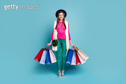 Full length body size view of her she nice attractive lovely cheerful cheery girl carrying new things clothing isolated on bright vivid shine vibrant green blue turquoise color background