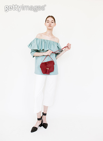 Beautiful young woman wearing stylish clothes and red designer bag Fashion model studio portrait on white background
