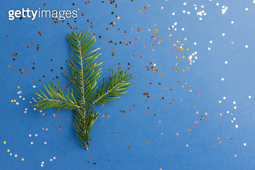 Sparkles with fir tree branch on blue trendy background. Festive backdrop for projects. Flat lay style. Top view. Color of the year.