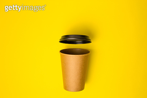 Open Craft paper cup with open lid on a yellow background. Flat lay. Creative Minimal food concept. Copy space, drink cup package mockup