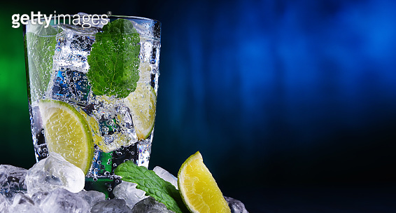 Glass of mineral water with ice, lime and mint