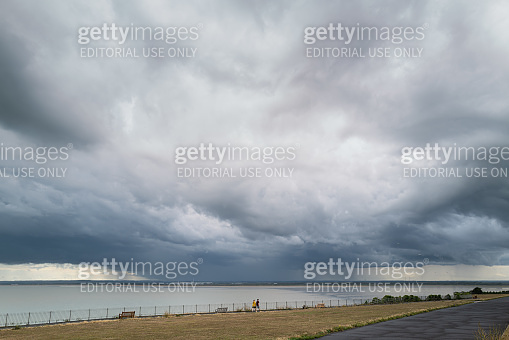 Storm clouds over Sandwich bay seen from the west cliff esplanade in Ramsgate. Two people walking on the promenade look tiny against the swell of the cloud.