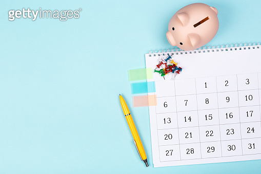 close up top view on white calendar 2020 month schedule to make appointment meeting or manage timetable each day lay on blue background for planning work and life concept