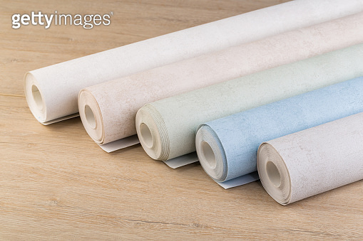 several rolls of multi-colored paper wallpaper on a wooden table