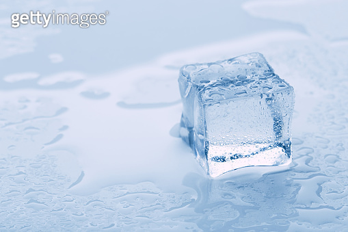 several melted ice cubes with drops on a light background with blue tinting