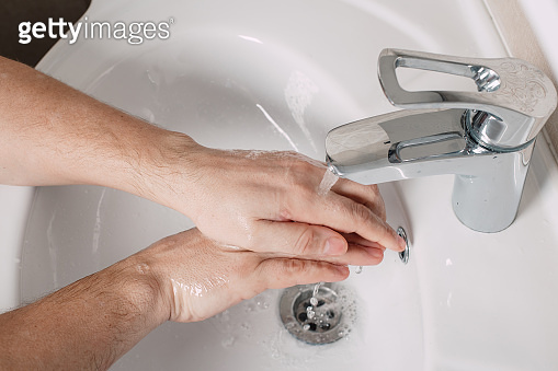 Wash hands under the tap with soap. Hygiene concept in detail. Beautiful stream of hands and water in the bathroom.