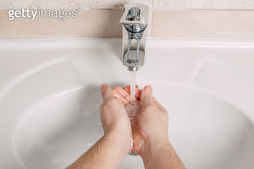 Washing hands under the water tap or faucet without soap. Hygiene concept detail. Beautiful hand and water stream in bathroom.