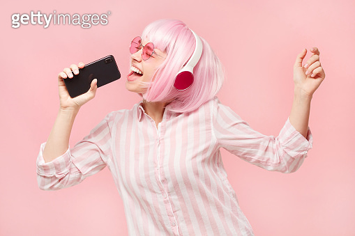 Happy teen girl holding phone and singing in online karaoke app, isolated on pink background