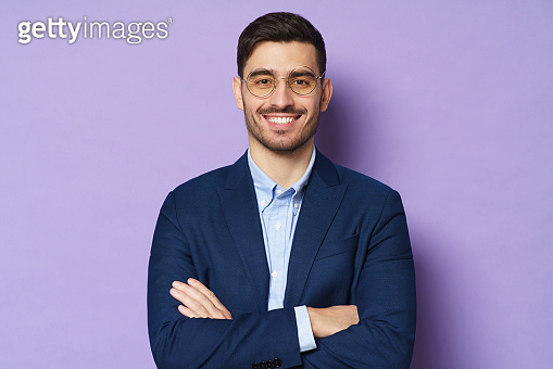 Portrait of handsome businessman in round eyeglasses standing in front of camera, looking with smile, holding arms crossed, ready to consult and support, isolated on purple background