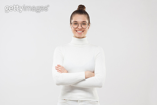 Young female professional wearing turtleneck and glasses, smiling with confidence, holding arms crossed, ready to support, isolated on gray background
