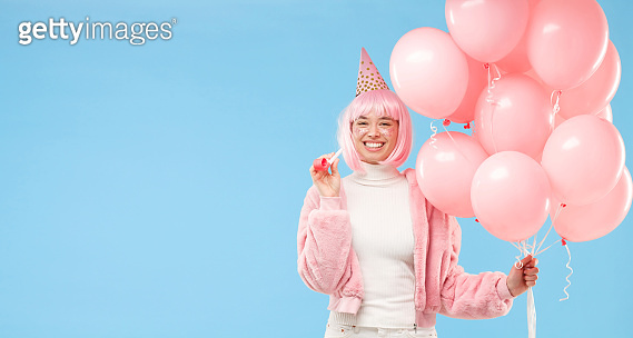 Banner of young birthday girl wearing pink fur coat, holding many balloons and whistle, isolated on blue background