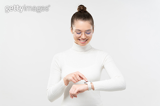 Young woman wearing eyeglasses and wristwatch, checking if she is in time, touching screen, smiling happily, isolated on gray background