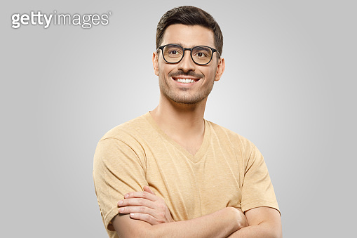 Photo of guy in beige T-shirt and glasses, looking aside with dreamful expression and smile, standing with arms crossed, isolated on gray background