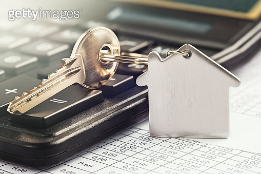 Real estate and investment concept. Calculator with finance blank, keychain with house symbol.