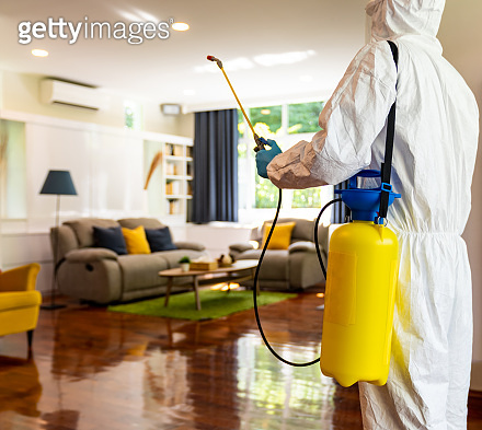 Asian man in PPE disinfection from COVID-19 at home