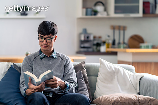 Asian young adult man reading fiction book at home