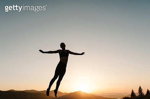 Happy woman jumping and enjoying life at sunset in mountains. Girl doing fitness exercise sport outdoors in the morning. Healthy lifestyle concept. Freedom, risk, challenge, success.